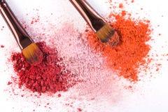 Los cepillos del maquillaje con se ruborizan o sombreador de ojos de tonos rosados, rojos y coralinos asperjado en el fondo blanc Fotografía de archivo libre de regalías