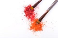 Los cepillos del maquillaje con se ruborizan o sombreador de ojos de tonos rosados, rojos y coralinos asperjado en el fondo blanc Imagen de archivo libre de regalías