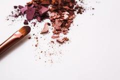 Los cepillos del maquillaje con se ruborizan o sombreador de ojos de tonos rosados, rojos y coralinos asperjado en el fondo blanc Fotografía de archivo
