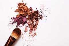 Los cepillos del maquillaje con se ruborizan o sombreador de ojos de tonos rosados, rojos y coralinos asperjado en el fondo blanc Imágenes de archivo libres de regalías