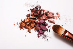 Los cepillos del maquillaje con se ruborizan o sombreador de ojos de tonos rosados, rojos y coralinos asperjado en el fondo blanc Imagenes de archivo