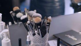 Los cepillos del maquillaje están en una taza del almacenamiento la mano femenina con los clavos púrpuras escoge un cepillo y sac almacen de metraje de vídeo