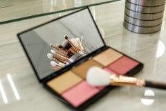 Los cepillos del maquillaje se reflejan en un espejo de la paleta con las sombras fotos de archivo