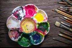Los cepillos y el extracto colorido colorea la plataforma usada los pintores en viejo Fotografía de archivo libre de regalías