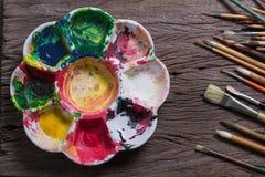 Los cepillos y el extracto colorido colorea la plataforma usada los pintores en viejo Foto de archivo