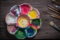 Los cepillos y el extracto colorido colorea la plataforma usada los pintores en viejo Imagen de archivo libre de regalías