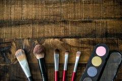 Los cepillos y el rimel del maquillaje fijaron en la tabla de madera Fotografía de archivo