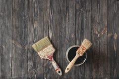 Los cepillos y las latas viejos de la pintura se ennegrecen en la tabla envejecida Fotos de archivo libres de regalías
