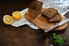 Los cereales empanan con las semillas cocidas en casa, los bio ingredientes, nutrici?n sana Pan de centeno cortado en tabla de co fotos de archivo