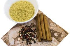 Los cereales en las placas, canela, especias, mezclan las pimientas en una servilleta aislada Foto de archivo