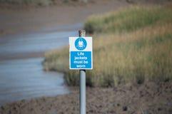 Los chalecos salvavidas deben ser advertir la muestra por el río fotos de archivo