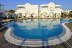 Los chalets blancos del centro turístico de lujo sobre piscina azul riegan Imagen de archivo libre de regalías
