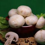 Los champiñones blancos mienten en un plato hermoso en un fondo verde imagen de archivo