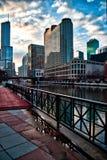 Los charcos reflejan paisaje urbano en Chicago después de una tormenta del invierno, como nubes claramente y el sol comienza a fi foto de archivo