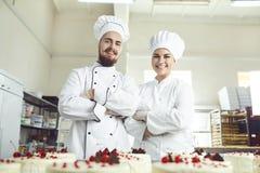 Los chefs de repostería en el uniforme blanco están sonriendo en la panadería foto de archivo