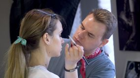 Los chillidos del individuo hacen maquillaje a la muchacha almacen de metraje de vídeo