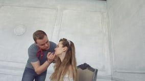Los chillidos del individuo hacen maquillaje a la muchacha metrajes