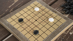 Los chinos juego de mesa van o de Weiqi Piedras blancos y negros y pequeño tablero hecho a mano Imagen de archivo