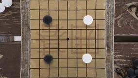 Los chinos juego de mesa van o de Weiqi Piedras blancos y negros y pequeño tablero hecho a mano Foto de archivo libre de regalías