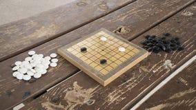 Los chinos juego de mesa van o de Weiqi Piedras blancos y negros y pequeño tablero hecho a mano Fotos de archivo