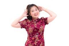 Los chinos que llevan de la mujer asiática joven visten el cheongsam tradicional con el gesto de la enhorabuena, Fotografía de archivo