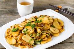 Los chinos sofríen las rebanadas del arroz pegajoso y el plato vegetal listos a foto de archivo