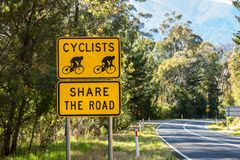 Los ciclistas comparten la señal de tráfico imagen de archivo