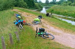 Los ciclistas en el río costean, las bicicletas turísticas mienten en la tierra Foto de archivo