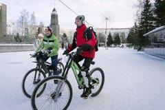 Los ciclistas montan en el cuadrado del invierno de la ciudad de Krasnoyarsk en el fondo del reloj principal de la ciudad imagen de archivo libre de regalías
