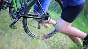 Los ciclistas que empujan las bicis suben una colina almacen de metraje de vídeo
