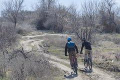 Los ciclistas son el montar las bicis en un camino abierto en la primavera fotos de archivo