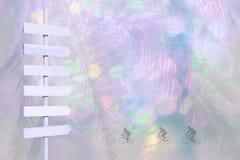 Los ciclistas y la flecha de madera señalizan en rosa borroso de las luces de la violeta y del color suavemente Fotos de archivo libres de regalías