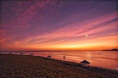 Los cielos púrpuras de la puesta del sol en la miel del océano de la playa están en la luna de par en par Foto de archivo