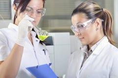 Los científicos jovenes atractivos de los estudiantes del doctorado que observan el color desplazan después del destillation de l imagen de archivo