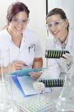Los científicos jovenes atractivos de los estudiantes del doctorado que observan el color desplazan después del destillation de l fotos de archivo