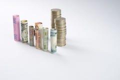 Los cientos dólares de EE. UU. y la otra moneda rodaron billetes de banco de las cuentas, con las monedas apiladas Imágenes de archivo libres de regalías