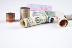 Los cientos dólares de EE. UU. y la otra moneda rodaron billetes de banco de las cuentas, con las monedas apiladas en blanco Imagen de archivo libre de regalías