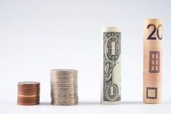 Los cientos dólares de EE. UU. y la otra moneda rodaron billetes de banco de las cuentas, con las monedas apiladas en blanco Fotografía de archivo libre de regalías