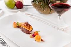 Los ciervos cocidos cortan con la salsa de Jus y las verduras de raíz con el vidrio de vino tinto fotografía de archivo libre de regalías