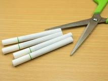 Los cigarrillos en fondo de madera con concepto de las tijeras paran humo Imagen de archivo