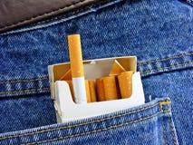 Los cigarrillos en pantalones vaqueros mueven hacia atrás el bolsillo Imagen de archivo