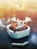 Los cigarrillos quemados están en cenicero Fotos de archivo libres de regalías