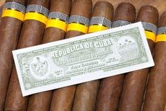 Los cigarros cubanos torcidos manualmente y el certificado de autenticidad fotografía de archivo libre de regalías