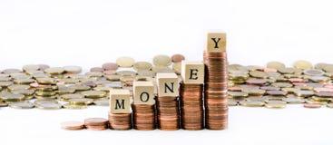 Los cilindros de monedas euro y el dinero de la palabra formaron por los pequeños cubos de madera Imágenes de archivo libres de regalías