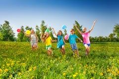 Los cinco niños felices con los globos corren en campo Imagen de archivo