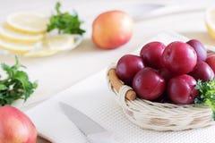 Los ciruelos jugosos mienten en una cesta en la tabla cerca de los melocotones jugosos y del limón cortado, comidas de la dieta,  foto de archivo libre de regalías