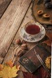 Los ciruelos, las nueces y las hojas con el cuaderno del vintage y el té con el filtro de la película efectúan vertical Imagen de archivo libre de regalías