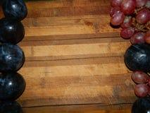 Los ciruelos y las uvas azules grandes en los lados de la cocina de madera suben Imagen de archivo libre de regalías