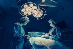 Los cirujanos combinan el trabajo con la supervisión del paciente en sala de operaciones quirúrgica Aumento del pecho Foto de archivo