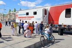 Los ciudadanos donan sangre en un día de verano en un punto móvil en la c imagen de archivo libre de regalías